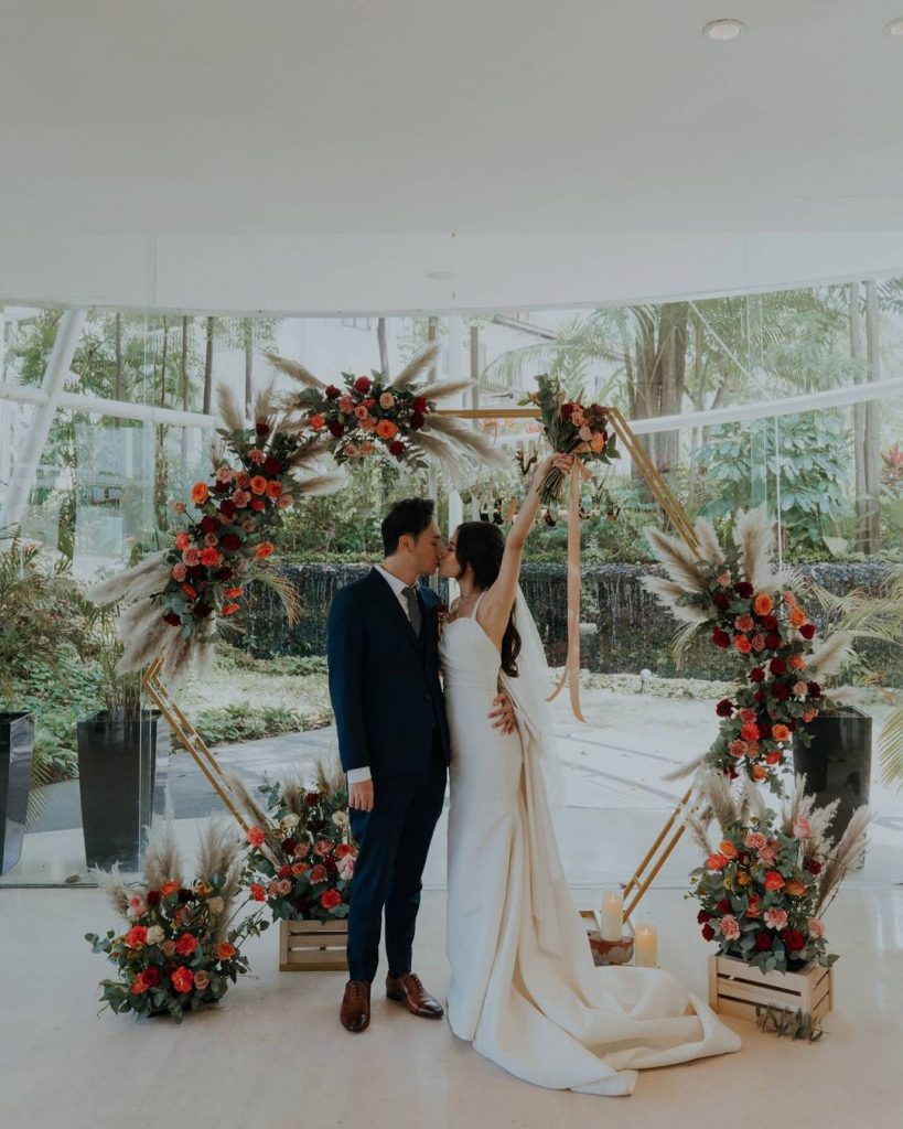 bride and groom kissing in front of a floral arch