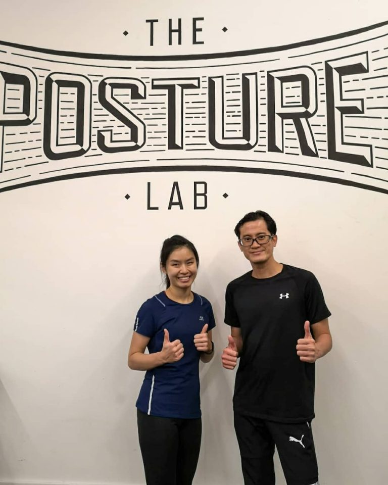 couple standing in front of the Posture Lab logo