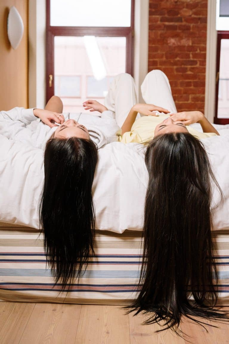 two women lying on the bed with their hair hanging down